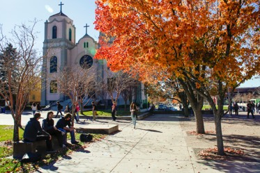 Students sitting outside St. Cajetan Church on campus