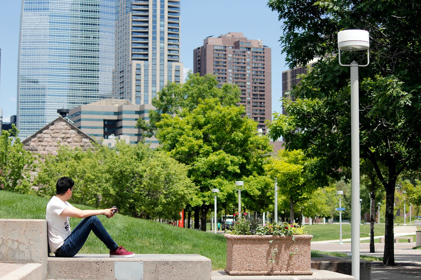 Student sitting outside looking at Denver skyscrapers and trees