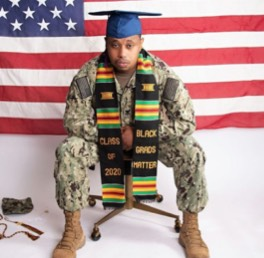 Student in military garb and graduation cap with a scarf that says
