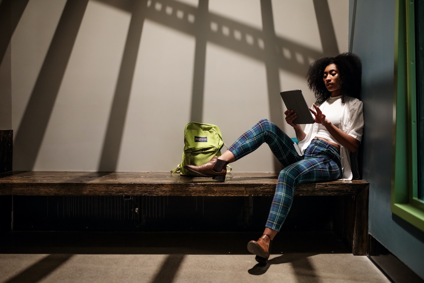Stylish woman holding tablet & sitting on a bench