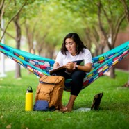 Woman in a hammock with a notebook and bag