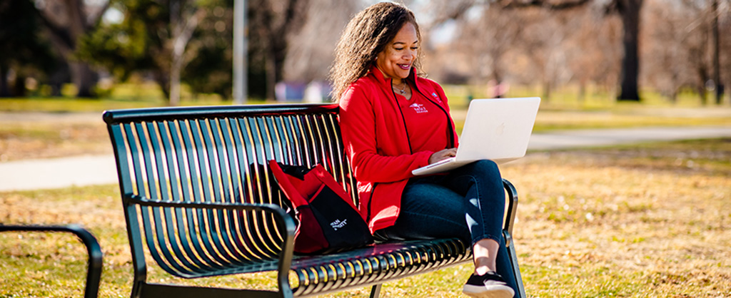 Woman in MSU Denver clothing sitting on a bench with her computer