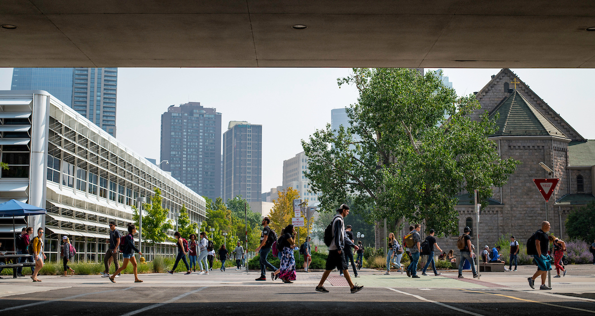 Students walking on campus in front of the Auraria library
