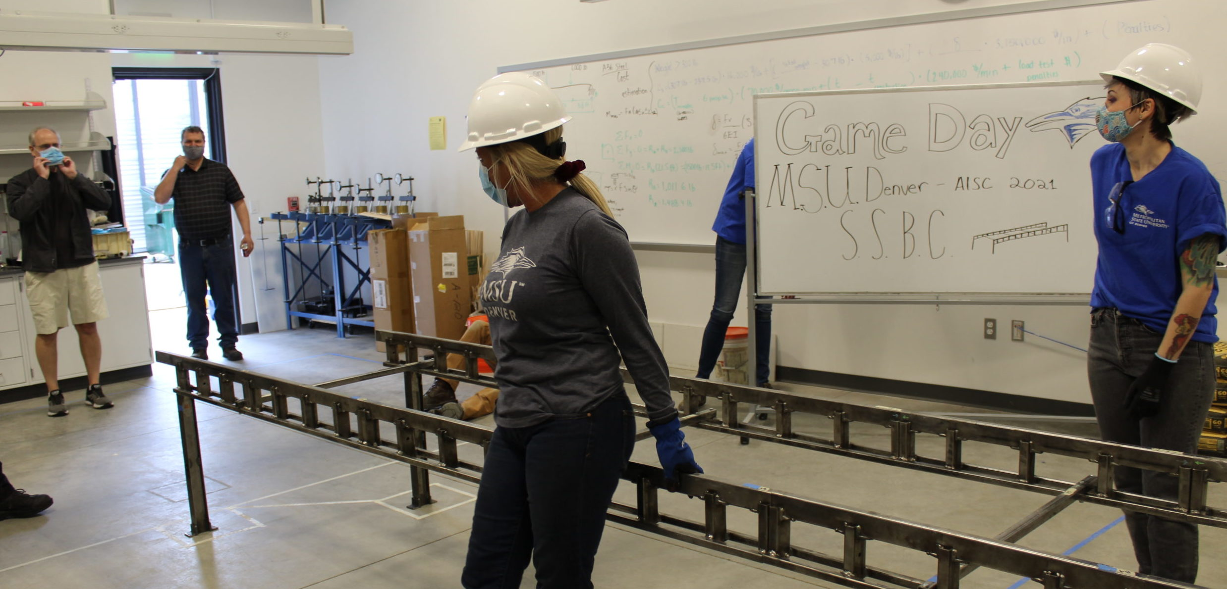 Students in MSU Denver clothing wearing hardhats at Game Day