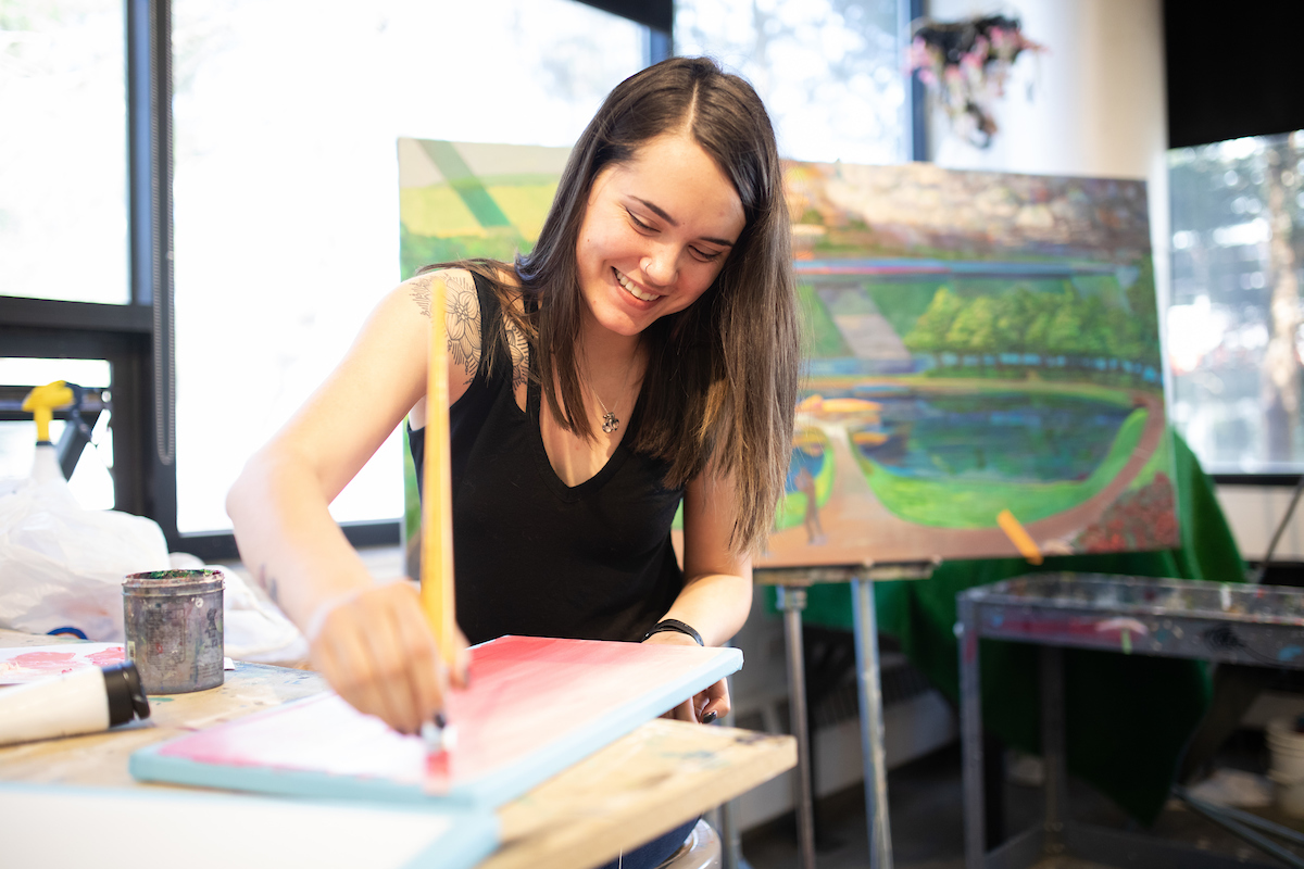MSU Denver student painting on a canvas