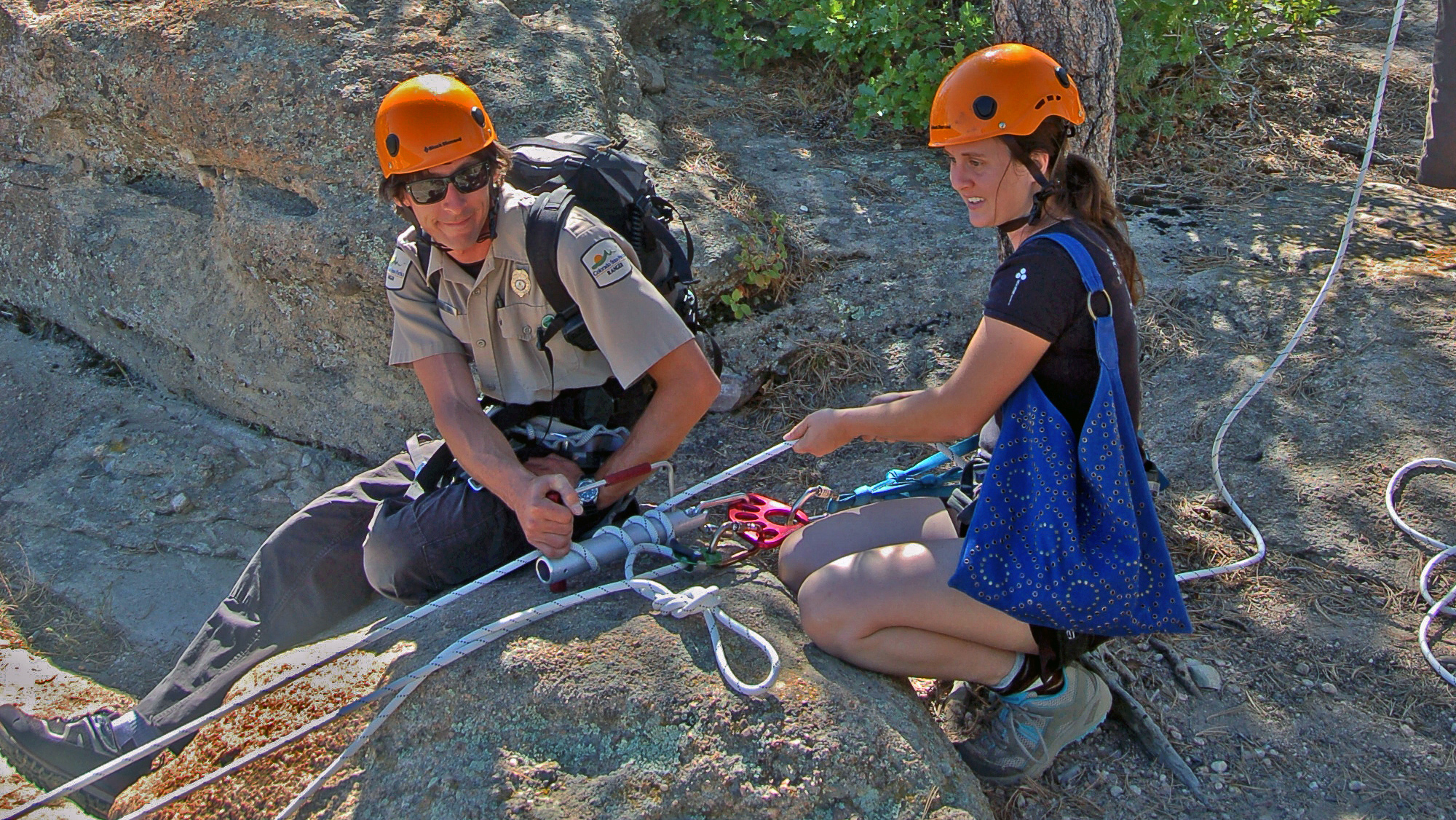 Two people using a belay device