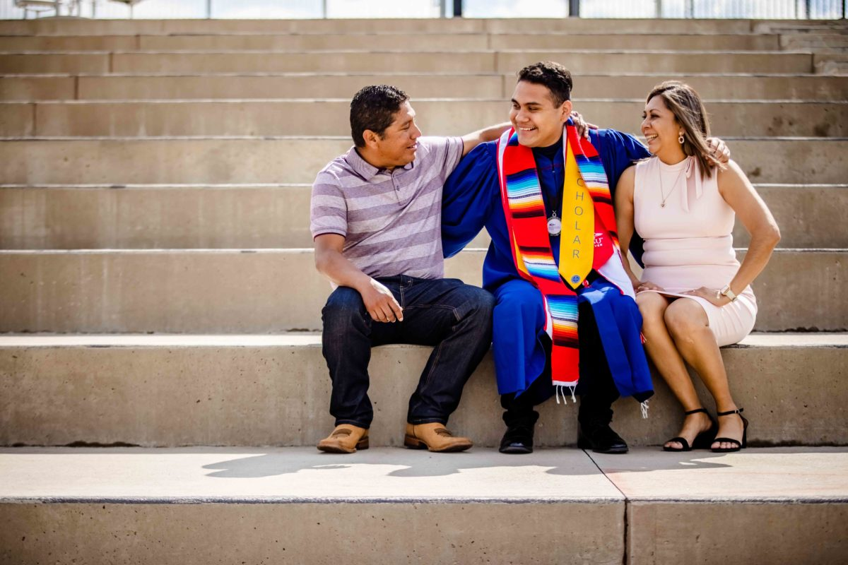 A graduate sitting on a set of stairs with their family