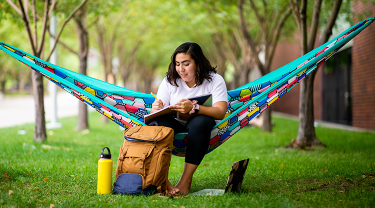 A student studies on a hammock on Auraria Campus.