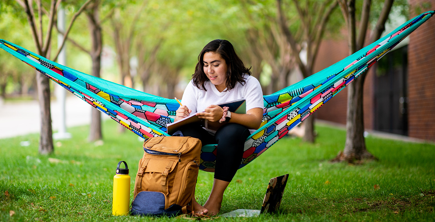 A student studying on a hammock outdoors.