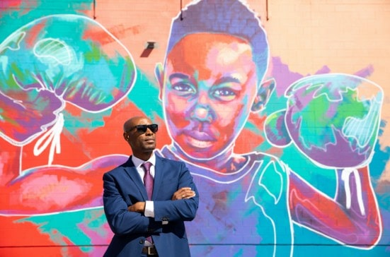 man in sunglasses in front of colorful mural
