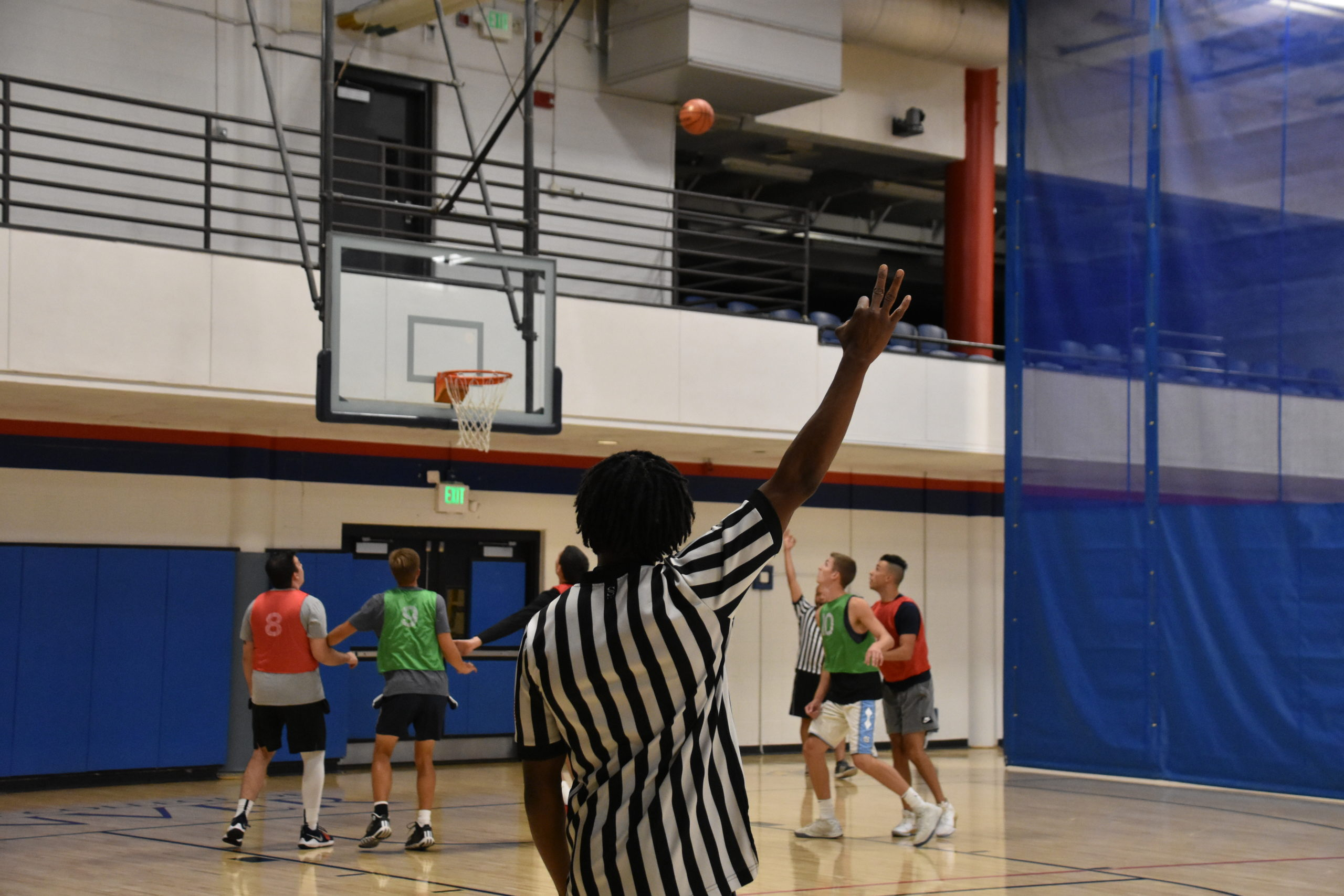 Intramural basketball official showing a 3 point attempt