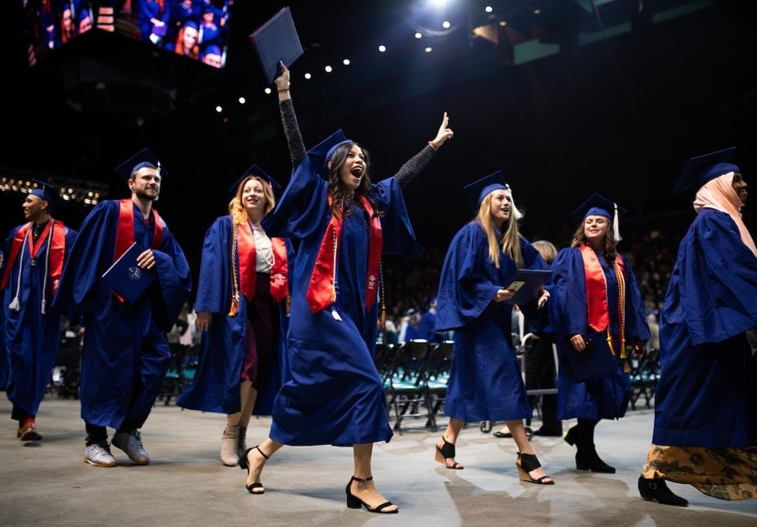 MSU Denver graduates walk off the Commencement stage with their diplomas.