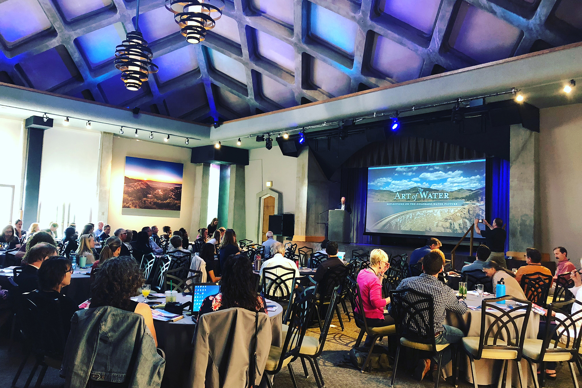 Wide shot of a conference with someone presenting
