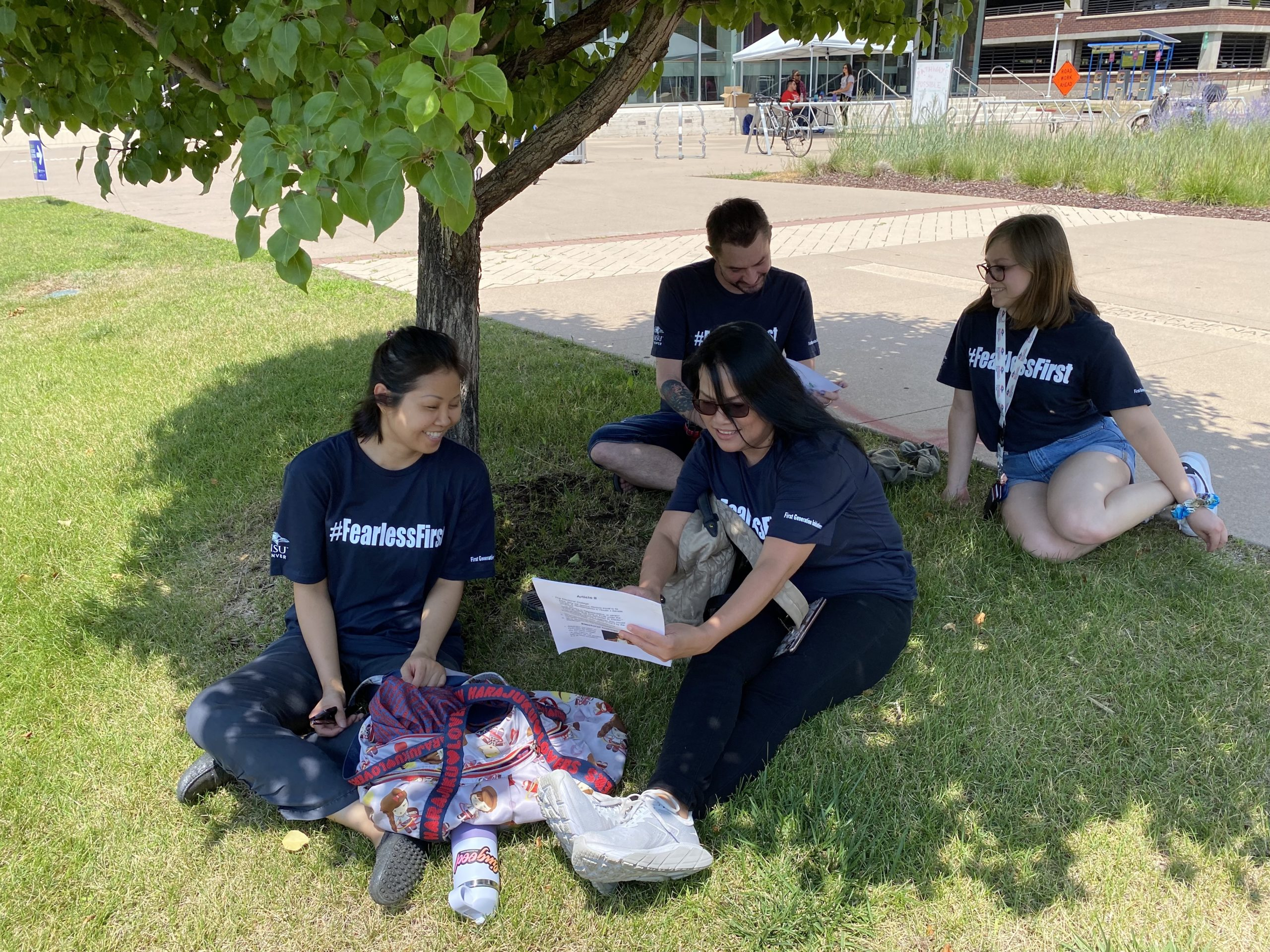 students talking under a tree on campus
