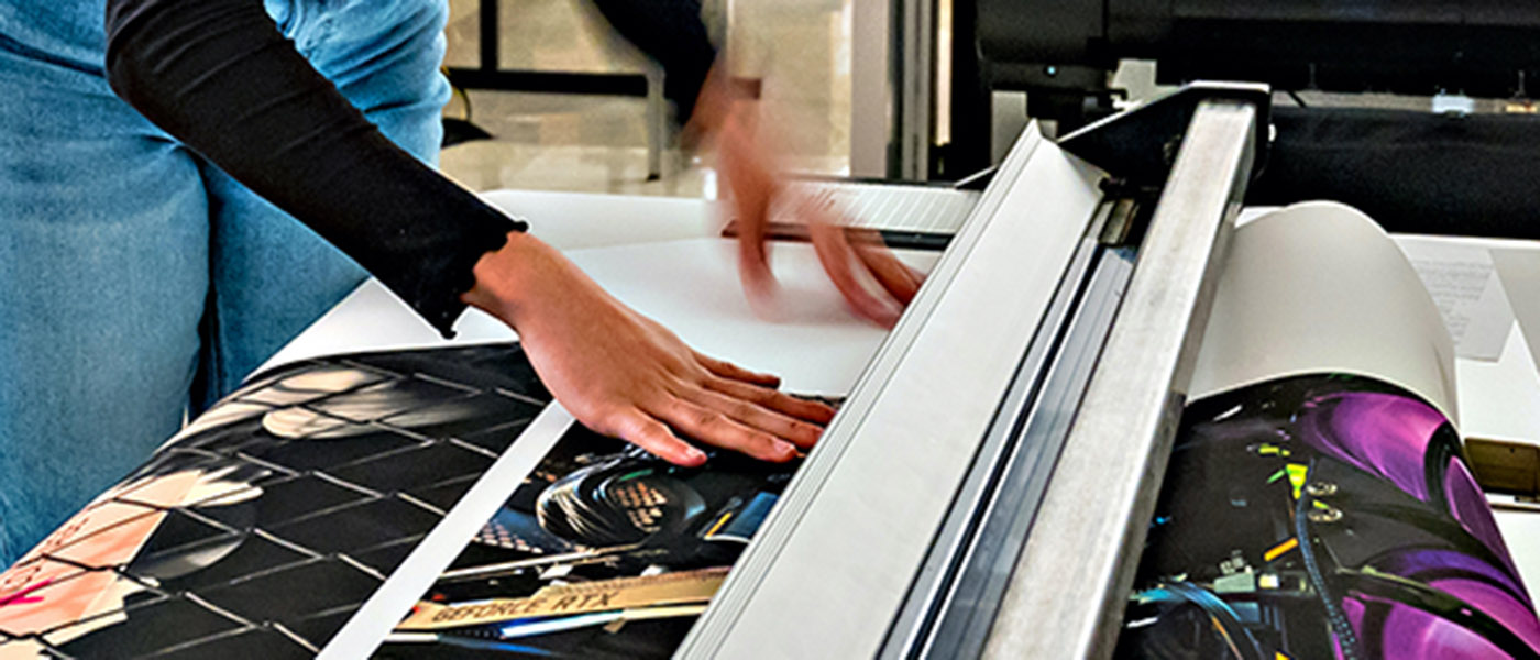 Cutting a large sheet of paper covered in artwork