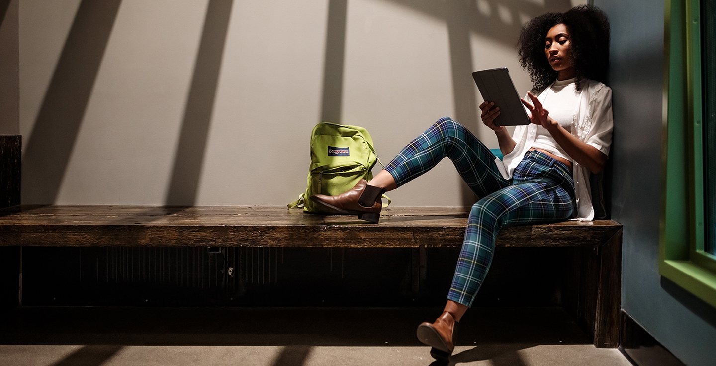 Student sitting on a bench inside studying