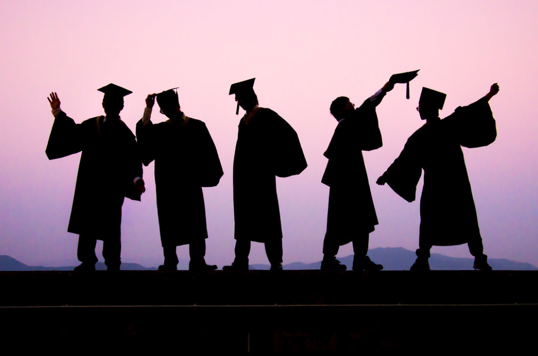 Five shadows of graduating students in commencement regalia