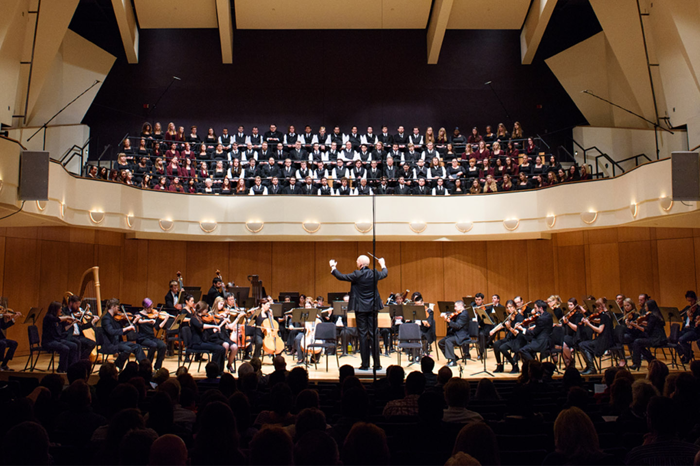 Full symphony orchestra and choir performing in the King Center Concert Hall