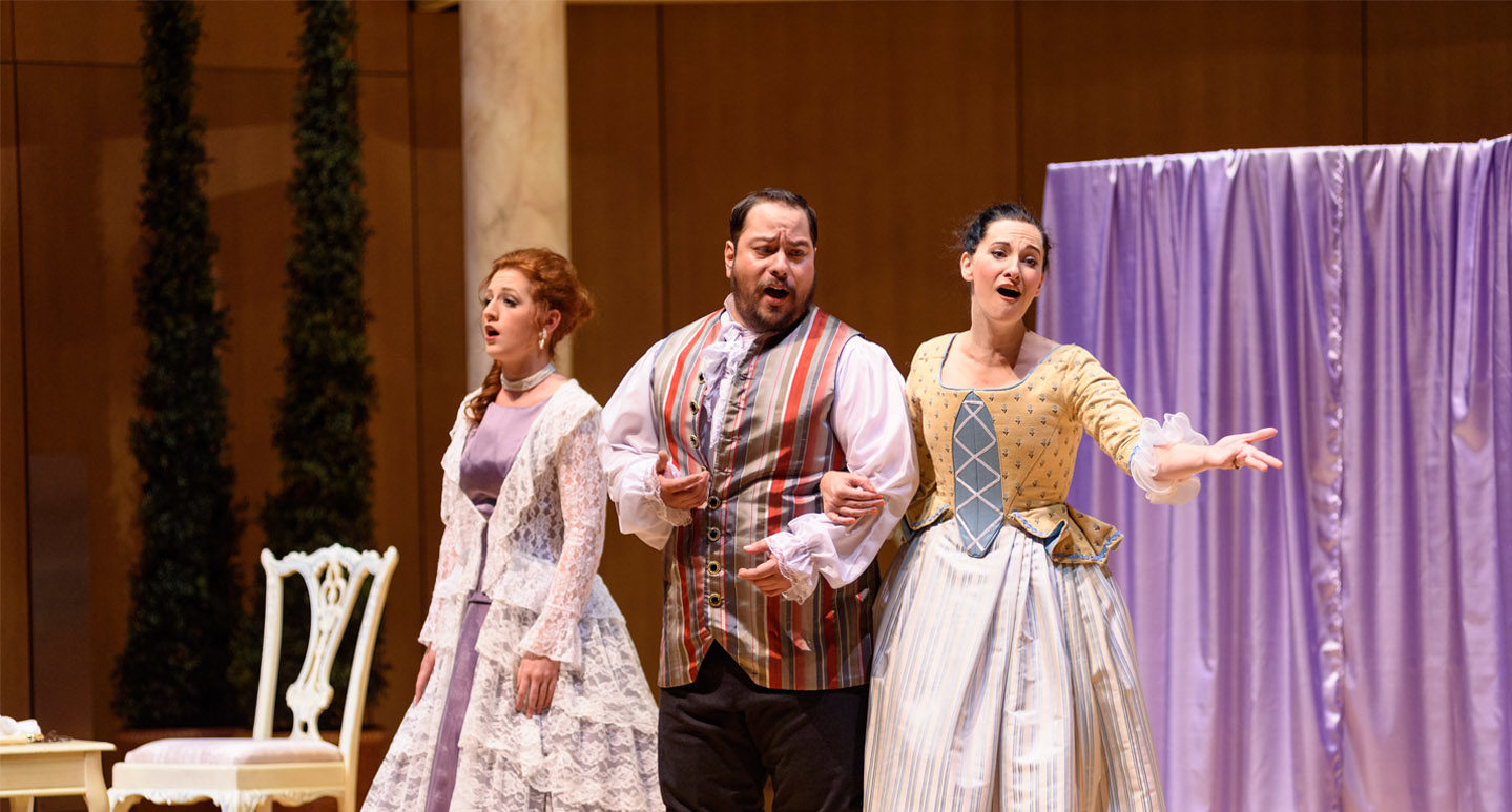 Three opera singers on stage performing Figaro in period costume