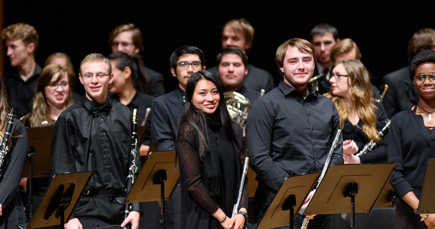 Flute section of a symphonic band standing and smiling after a performance